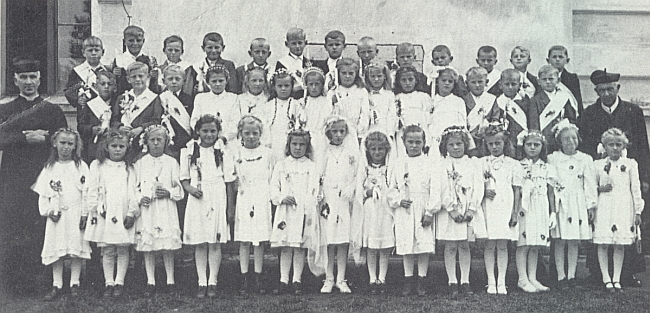 První a také poslední svaté přijímání dětí německých obyvatel Rychnova nad Malší v roce 1945, kde děkan Glockner stojí s biretem na hlavě zcela nalevo zřejmě před místním kostelem