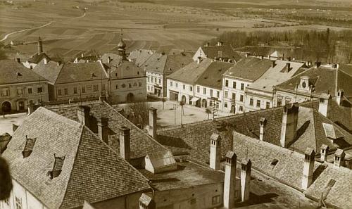 Pohlednice českokrumlovského fotoateliéru J. Wolfa zachycuje dům čp. 45     na novohradském náměstí (vlevo od radnice s věžičkou)