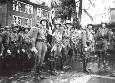 """Přísaha """"útočných oddílů"""" Freikorps v Bavorské Železné Rudě a jejich nástup na Kostelním náměstí už v té """"české"""" svědčí o tom, jakým tlakům Československo v roce 1938 čelilo zevně i uvnitř"""