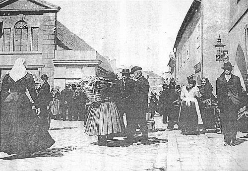 """Německý selský živel jazykového ostrova kolem Budějovic tu zaplňuje Masnou ulici (Fleischgasse), jak se tehdy nazývala část dnešní Hroznové ulice před Masnými krámy, naproti kterým ještě nestála budova Městské spořitelny (otevřena 1913) a za nimiž jen hospoda """"U tří sedláků"""" svým názvem připomíná ty, kdo jsou na spořitelně v německém kroji vyobrazeni (pohlednice z přelomu 19.-20. stol.)"""
