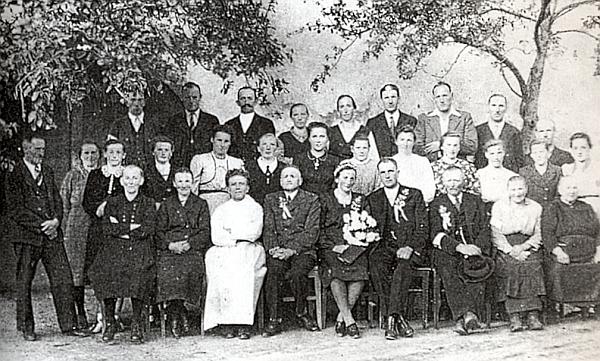 """Na svatbě """"Jungwirthn-Marie"""" v Rychnůvku někdy za dnů pozdního podzimu roku 1946, kdy už byli mnozí místní odsunuti doRakouska a do Německa, sedí v prvé řadě třetí zleva"""