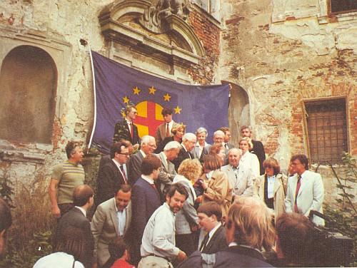 Na zpustlém nádvoří poběžovického zámku zakladatele panevropského hnutí Richarda Coudenhove-Kalergi v roce 1990 je zachycen pod vlajkou Panevropy v šedém saku i Karel Groulík se svým přítelem Berndem Posseltem (s černou vázankou)
