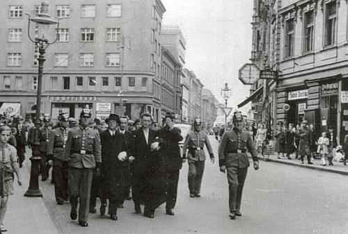"""Příslušníci říšské policie vedou v roce 1938 ulicemi Chebu zatčené místní """"disidenty"""" nejrůznější provenience"""