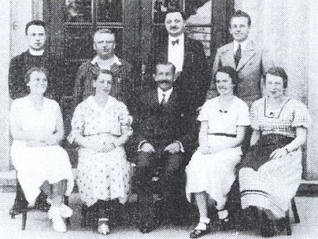 Pan řídící Grundl sedící uprostřed před budovou školy ve Větřní sučitelským sborem v roce 1934 (druhý zleva tu stojí Karl Müller)