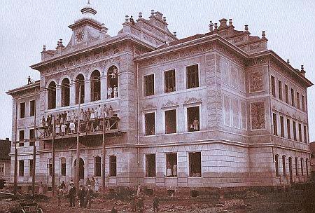 Budova prachatického gymnázia před dokončením r. 1897 na snímku, po jehož pořízení se lešení nad vchodem zřítilo, zabilo jednu z žen a několik dělníků zranilo