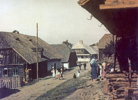 Kolorovaná pohlednice zachytila vesnickou ulici ve Stodůlkách