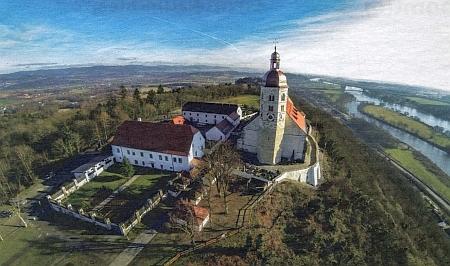 Letecký snímek poutního kostela na vrcholu hory Bogenberg, napravo s tokem řeky Dunaje