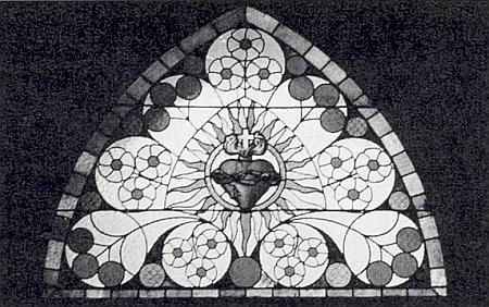 Velké skleněné okno nad severním portálem rožmitálského kostela se znázorněním Nejsvětějšího srdce Ježíšova