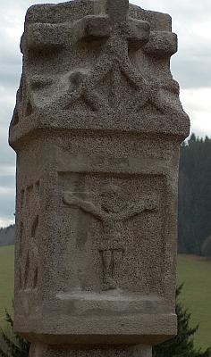 Boží muka s reliéfem Ukřižovaného, pocházející snad z roku 1521, zachycena v detailu a na pozadí jejího rodného domu, přestavěnézdejšíškoly