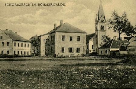 Stará pohlednice z Černé v Pošumaví zachycuje vlevo od kostela školu, vpravo pakdům čp.28...