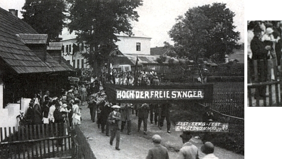 """Ten starý muž s bílým knírem vepředu vlevo je sklář Adolf Halletz, řečený """"Napulion"""", na ruce nese ročního vnoučka Karla Halletze, zatransparentem """"Hoch der freie Sänger"""" kráčí průvod pěveckého dělnického spolku v Arnoštově, kde se jeho slavnost konala 13. srpna roku 1930"""