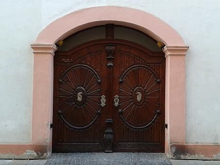 Vrata průjezdu v přízemí severní části někdejší piaristické koleje v Biskupské ulici