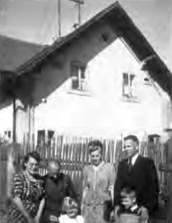 Snímek z roku 1950 zachycuje rodinu Josefa Hamperla, propuštěného na Velikonoce 1947 z amerického zajetí, před domem ve Waidhausu - malý Wolf-Dieter stojí před otcem