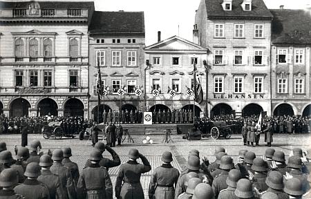 Firma na domě zůstala, jak patrno i z tohoto neblahého snímku přísahy nových vojáků wehrmachtu dne 2. března 1941 za hojné účasti obyvatel na náměstí, kde jsme v srpnu 1968 mohli z nakladatelství Růže právě z těch vyšších oken nejvyššího domu v řadě sledovat okupanty sovětské