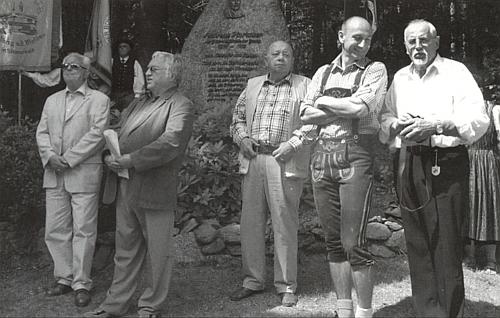 Tady vidíme Rudolfa Hartauera druhého zleva vedle Franze Payera (zcela vlevo) jako řečníka v červenci roku 2014 při příležitosti 175. výročí narození Andrease Hartauera u jeho památníku v bavorské obci Mauth na snímku, provázejícím v krajanském časopise text tam proneseného projevu (zcela vpravo stojí na snímku Ingo Hans)