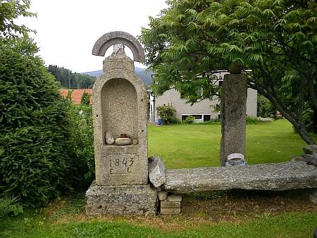 Boží muka a kříže z okolních zaniklých obcí u jednoho ze tří dnes stojících domů v bývalé obci Bolechy