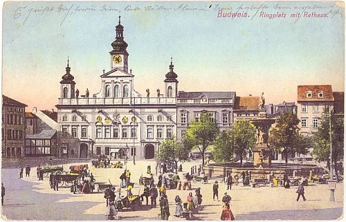 Rodné Budějovice na staré barevné pohlednici, které dodávají kolorit zejména venkované, nabízející kolem Samsona své zboží z vozů i vozíků, v roce Hawelkova narození dosud jediných prostředků dopravy