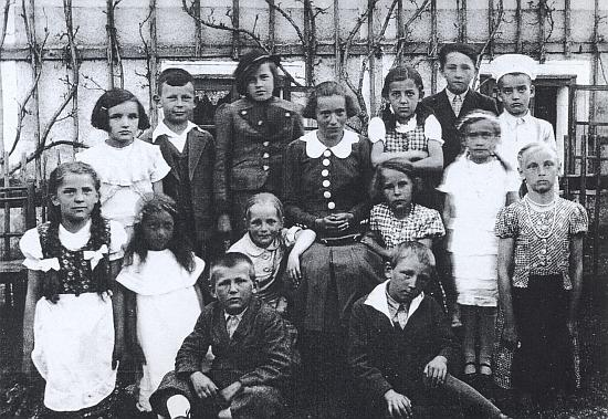 Účinkující školního představení v Kapličkách - on sedící vlevo dole, v zadní řadě stojící hoch s rozhalenkou druhý zleva syn pan řídícího Bitzana