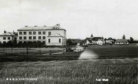 """Strýčice s českou """"jubilejní"""" školou, kde byla za války ubytována v rámci tzv. Říšské pracovní služby (RAD),     na staré pohlednici fotoateliéru Wolf (viz i Matthäus Kraupatz)"""