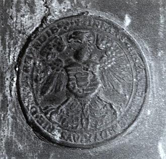 """Pod medailonem je umístěna zvonová pečeť, odkazující nápisem """"Infans Hispanien . Archidux Austrie . Dux Burgundie"""" ke jménu císaře Svaté říše římské a českého krále Maxmiliana II., jehož synem a nástupcem byl Rudolf II., stejně jako otec velice tolerantní vůči protestantismu"""
