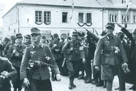 """Na snímku z nacistické propagační publikace vchází oddíl horských myslivců v říjnu roku 1938 """"za nadšení obyvatel"""" do Horní Plané"""