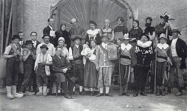 """Na snímku z uvedení hry """"Im Banne des Hochwalds"""" ve Frymburku v roce 1935, jejíž autor, děkan Petrus Dolzer, sedí před herci vpředu, vidíme mladého Hanse Hölzla stát druhého zleva s obličejem zčásti zakrytým kloboukem muže před ním"""
