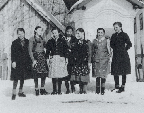 Tady vidíme Rosu Riedlovou někdy za války ve skupině děvčat z rodné vsi, stojící třetí zprava ve sněhu přivýklenkové kapli nápadně podobné té spramenem při hoře Kmet