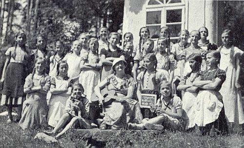 """Školačky ročníku 1922-1924 z Jablonce se svou učitelkou Marií Pöschikovou před studánkou při """"Altenbergkapelle"""", jejíž voda prý léčila zrak"""
