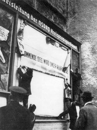 Odstraňování propagandistické tabule NSDAP z Černé věže v Českých Budějovicích v květnových dnech roku 1945     (v místech za nacisty odstraněným Myslbekovým pomníkem biskupa Jirsíka)