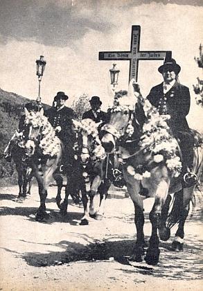 """Selská """"svatodušní jízda"""" u Kötztingu v čele s křížem, nesoucím nápis Ježíš Nazaretský, král židovský"""