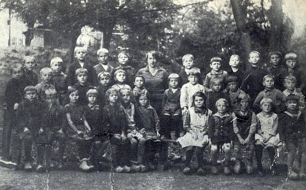 Lenorští školáci ročníků narození 1921 a 1922 s paní učitelkou Ulrychovou na snímku, kde je jako čtvrtý zprava v zadní řadě zachycen i on