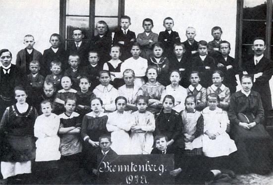 Na snímku z roku 1921 je zachycen stojící vlevo sesedící při něm manželkou a školními dětmi z tehdejšího Brenntenbergu (i v češtině zvaného Brentenberg), až vroce 1949 přejmenovaného na Spálenec