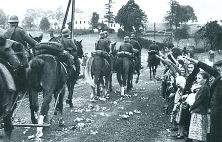 Děvčata a ženy zasypávají na snímku z nacistické propagační publikace před československou celnicí     u osady Silnice (Landstrassen) u Strážného cestu s vojáky wehrmachtu v říjnu 1938 květy