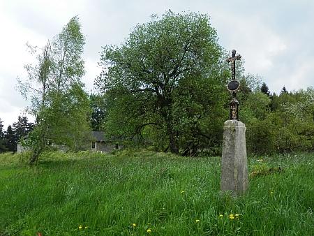 Obnovený křížek, v pozadí rodný dům
