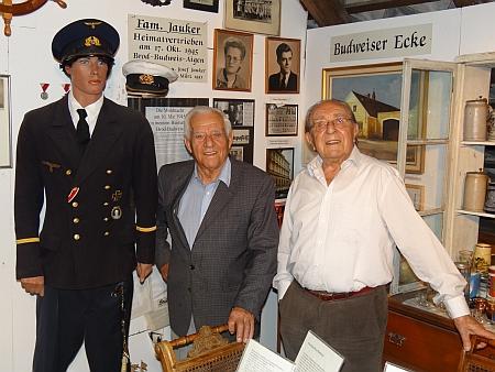 """V rodinném muzeu stojí tu vpravo Edmund Wiltschko, vlevo Josef Jauker pod snímkem své ženy Christl, roz.Pflegerové, kterou si vzal v březnu 1951 - vpravo na zdi pod nápisem """"Budweiser Ecke"""" lze zahlédnout obraz spůvodní podobou domu čp. 5 ve Vrátě (viz níže)"""