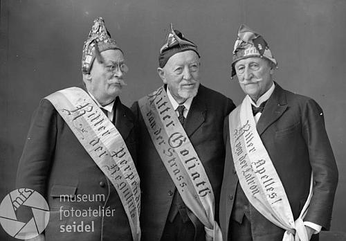 """Na snímku ze Seidelova fotoateliéru z února 1932 vidíme s pokrývkami hlavy spolku Schlaraffia zleva """"rytíře"""" Adolfa Jirku, Johanna Festla a Karla Schinko"""