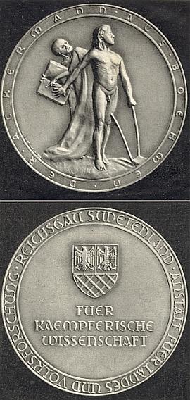 """Líc a rub tzv. Ackermannovy medaile """"za bojovnou vědu"""", kterou každoročně udílel od roku 1940 hejtman """"říšské župy Sudetenland"""" na veřejných zasedáních """"Sudetoněmeckého ústavu pro bádání o zemi a lidu"""" (na rubu medaile je i reliéf znaku """"říšské župy Sudetenland"""")"""