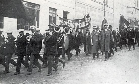 Raimund Kelnberger starší na dvou snímcích z manifestace německé sociální demokracie v ČSR, konané ve Vimperku roku 1937     - pod transparentem s heslem Naše vítězství-Váš chléb je to ten muž v černém, s černým kloboukem a motýlkem