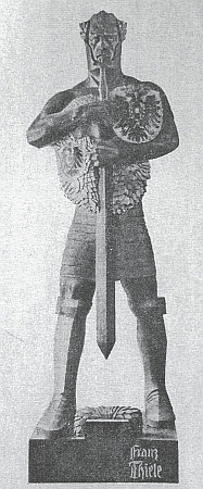 """Socha hraničářského bojovníka, zvaného """"Bundeswehrmann"""" - třímetrová socha Franze Thiela z lipového dřeva má na hrudi znaky rakouských a německých zemí a stojí na kamenném podstavci"""