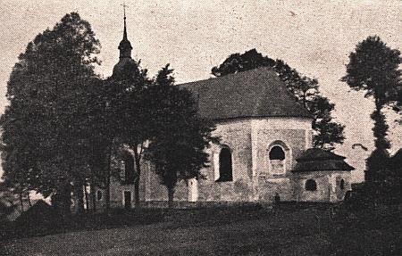 Kostel sv. Jana Nepomuckého v Nemanicích mezi stromy na starém snímku z krajanského časopisu