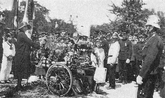 Křtí v Podražnici, dnes části města Horšovský Týn, novou hasičskou stříkačku, vlevo stojí se synem kněžna von und zu Trauttmansdorff-Weinsberg