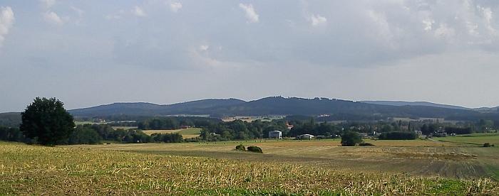 Kraj pod Blanským lesem - vpředu mezi stromy Záboří, nad ním pod Skalkou prosvítají stavení Holašovic, vlevo Švelhán (721m n.m.) a napravo na obzoru hřeben Kleti