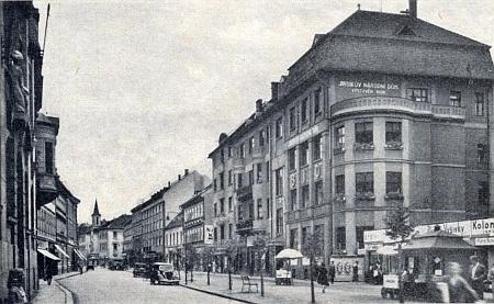 Průhled Lannovou třídou s Jirsíkovým národním domem v popředí asvěžičkou budovy německého gymnázia v pozadí na snímku zpředválečných dob