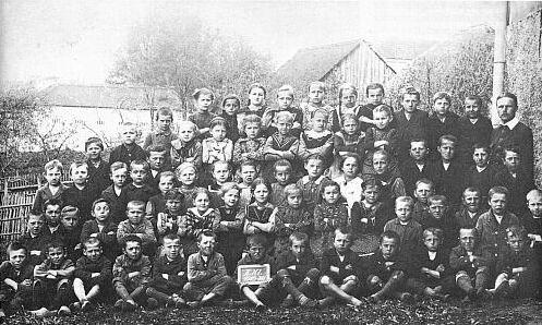 Se spolužáky z obecné školy ve Frymburku roku 1920 (v první řadě osmý zleva) apanem učitelem Franzem Peterem