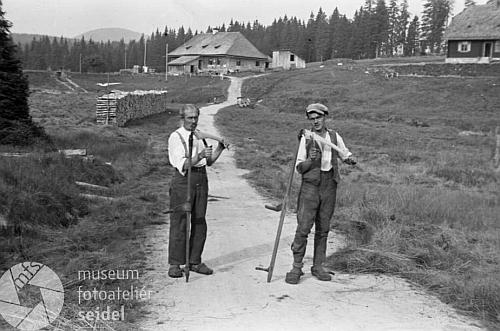 Tady figurují Franz Kortus mladší a starší na snímku z českokrumlovského fotoateléru Seidel s kosami před Roklanskou hájenkou v roce 1947
