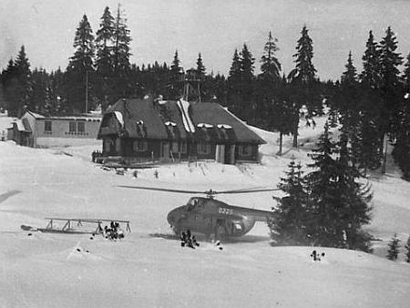 """Na fotografii někdy z poloviny padesátých let 20. století je vidět Roklanská chata, za ní budova """"roty""""     a pozorovací věž, v popředí vrtulník, který vojáky v zimě zásoboval"""
