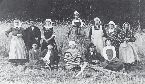 """Rodina Pascherova z chalupy zvané """"Pauli-Haus"""" v dnes zcela zaniklých Nižších Hodonicích i se sousedy na zčásti už pokoseném obilném poli"""