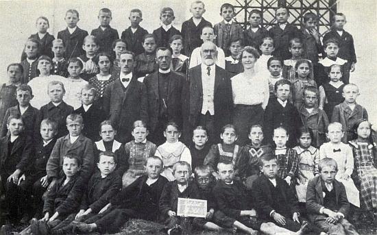 Jeho otec, řídící učitel Edmund Kraml s bílým plnovousem, uprostřed žáků školy v Záblatí