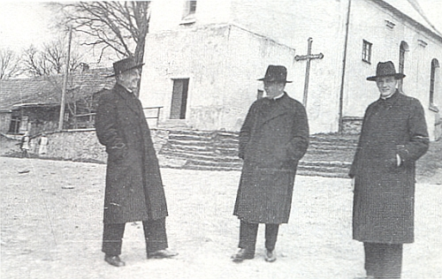 Stojí tu vpravo se dvěma schönstattskými kněžími před někdejším kostelem Nejsvětější Trojice ve Zhůří pod Javornou s misijním křížem při zdi