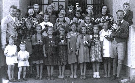 Stojí tu vlevo vepředu s obutými i bosými žákyněmi školy ve Strýčicích a jejich učitelkami a učiteli na konci válečného školního roku 1943/1944